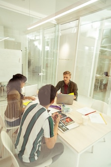 Internationale groep. knappe blonde man zit tegenover de computer en luistert naar zijn vrienden