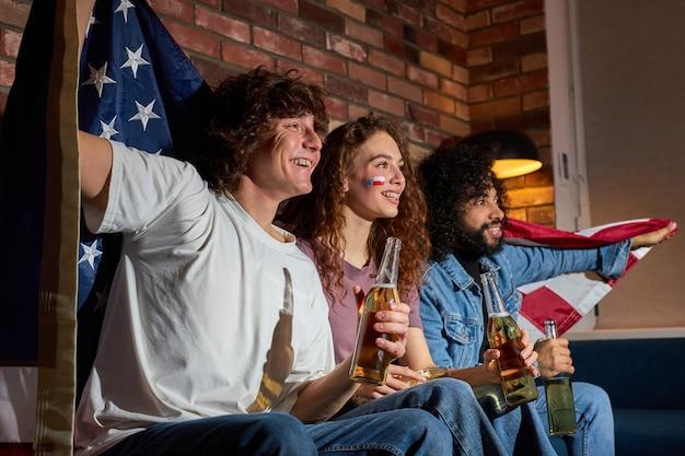 Internationale groep studentenvrienden die thuis rondhangen, ineengedoken op de bank, opgewonden kijkend naar het evenement op tv dat bier drinkt, anticiperend op het winnende doelpunt. amerikaans voetbal, basketbal, tennis