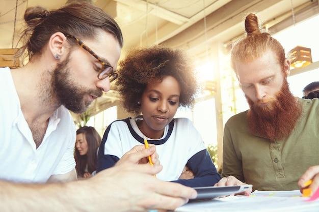 Internationale groep van drie managers die samenwerken aan een nieuw project, concept en plannen analyseren met behulp van digitale tablet.