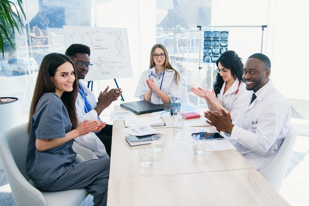 Internationale groep van professionele jonge artsen klappen in hun handen en glimlachen op een medische conferentie in een moderne kliniek
