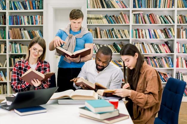 Internationale groep van vier gerichte slimme jonge studenten in casual outfits studeren in de moderne universiteitsbibliotheek, zittend aan tafel met boeken en laptop