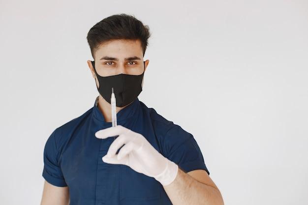 Internationale medische student. man in een blauw uniform. arts met een masker.