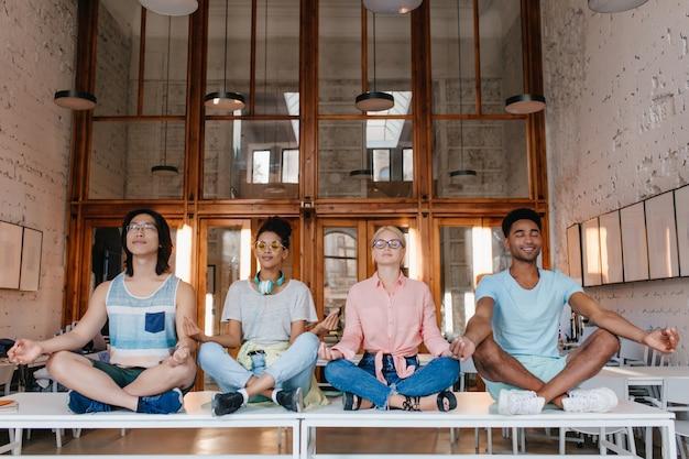 Internationale studenten mediteren op de bureaus in de bibliotheek, ontspannen voor examens. universiteitsvrienden doen yoga op de tafel met gesloten ogen.