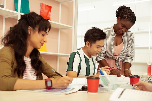Internationale studenten. vriendelijke aziatische student die aan tafel zit terwijl hij overlegt met zijn leraar