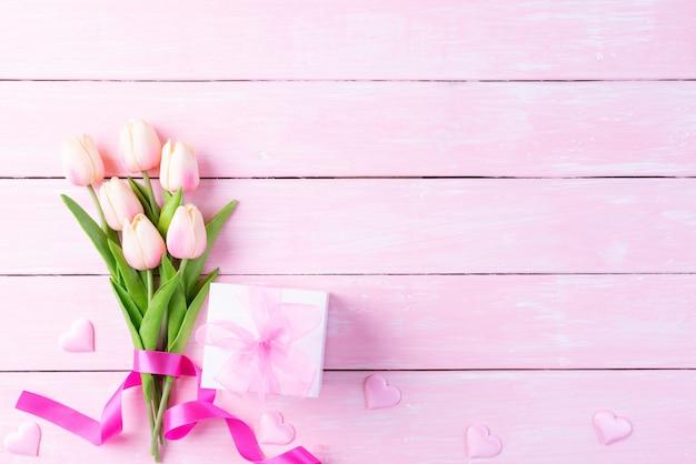 Internationale vrouwendag concept. roze tulpen en rood hart met geschenkdoos