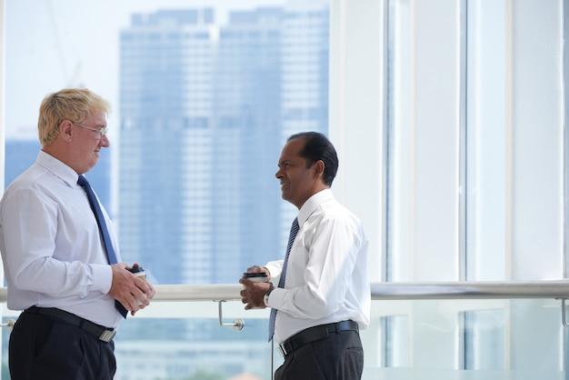 Internationale zakenpartners die elkaar ontmoeten op kantoorbalkon praten en koffie drinken