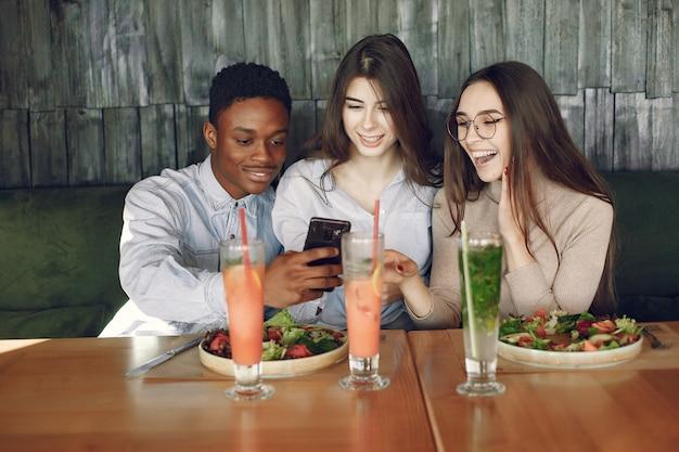 Internationals mensen aan tafel zitten met salades en cocktails
