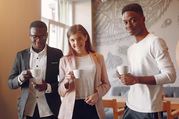 Internationals mensen praten in een café en drinken een kopje koffie