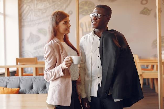Internationals mensen staan in een cafe en drinken een kopje koffie