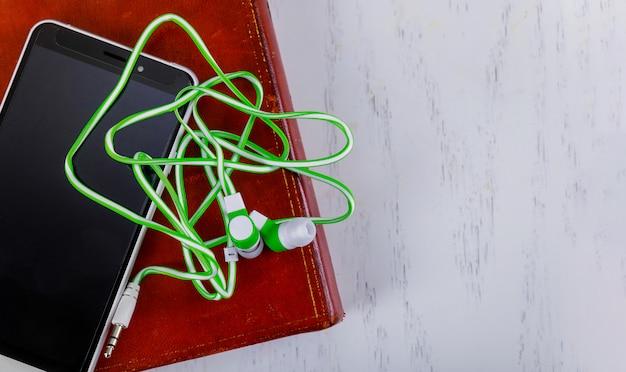 Internet ebook, smartphone, hoofdtelefoons op de achtergrond van een houten lijst audioboek.