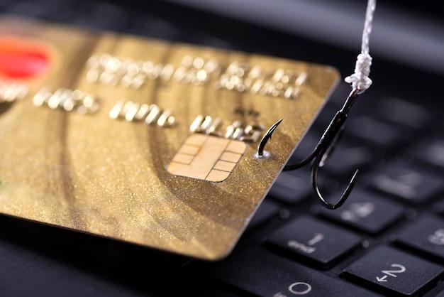 Internetfraude met behulp van computertechnologie, geld stelen op internet, creditcardgegevens stelen. haak vastgehaakte creditcard op laptop toetsenbordachtergrond.