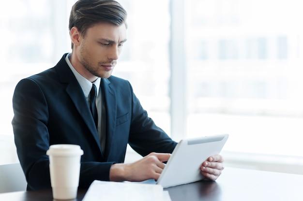 Internetgebruiker. vrolijke jonge man die digitale tablet gebruikt tijdens de koffiepauze op kantoor