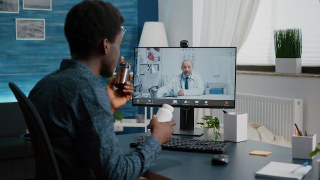 Internetgezondheidscontrole van zwarte man die praat met huisarts die telehealth-app gebruikt terwijl hij thuis zit. online medisch consult, videoconferentie van zieke patiënt, virtuele telegeneeskunde