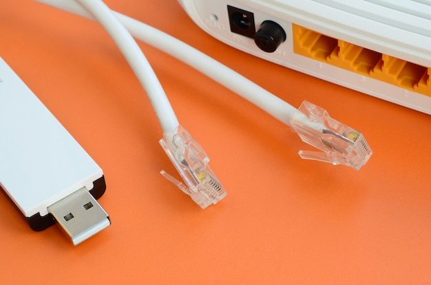 Internetrouter, draagbare usb-wi-fi-adapter en internetkabelstekkers liggen op een feloranje achtergrond.
