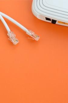 Internetrouter en internetkabelstekkers liggen op een feloranje achtergrond. items vereist voor internetverbinding
