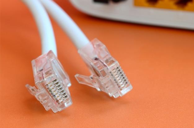 Internetrouter en internetkabelstekkers liggen op een feloranje achtergrond.
