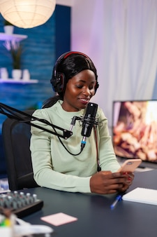 Internetshowhost beantwoordt vragen over het sms'en van fans aan de telefoon en praten met de microfoon vanuit de podcaststudio thuis. show productie uitzending presentator streaming live content opnemen van digitale media