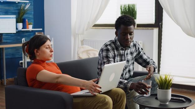 Interraciaal paar met zwangerschap die samen op de bank zitten