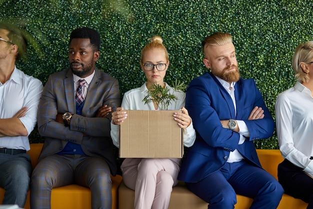 Interraciaal team van medewerkers die niet tevreden zijn met de komst van een nieuwe medewerker