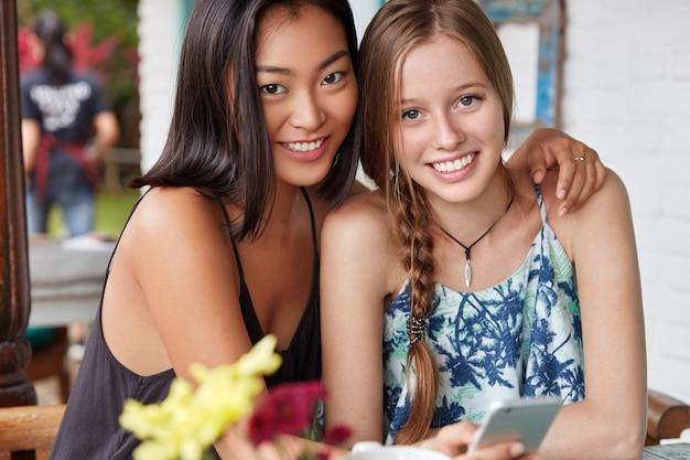 Interraciaal vriendschapsconcept. gelukkige jonge aziatische en europese vrouwen omarmen elkaar terwijl ze vrije tijd doorbrengen in de coffeeshop