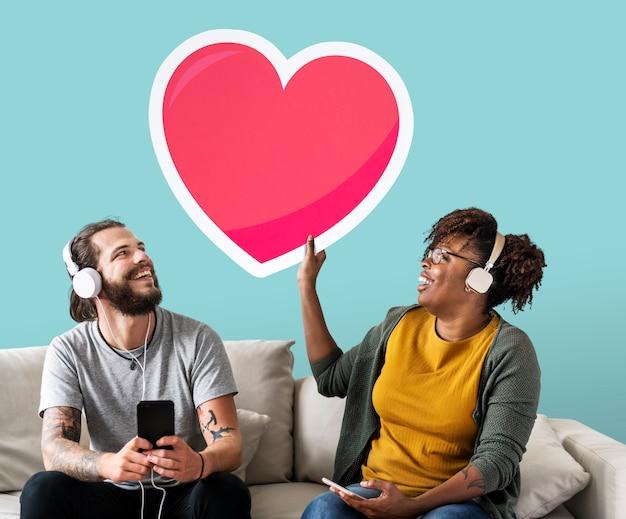 Interracial paar dat aan muziek luistert en een hart houdt emoticon