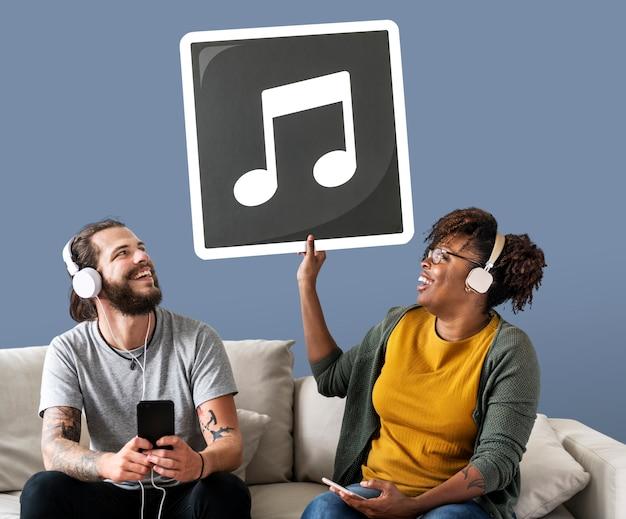 Interracial paar dat aan muziek luistert en een muzieknoot houdt