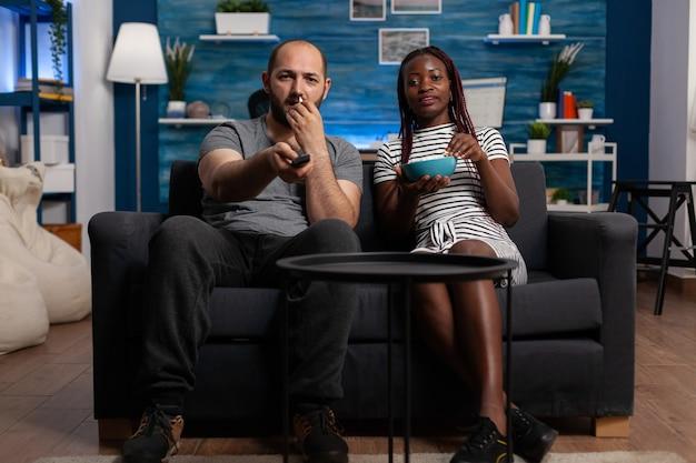 Interracial paar zitten samen op de bank thuis televisie te kijken. afro-amerikaanse vrouw die een kom popcorn vasthoudt terwijl een blanke man van kanaal wisselt met de afstandsbediening van de tv