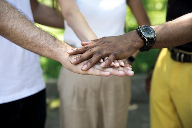Interracial vrienden die handen dicht tegenhouden