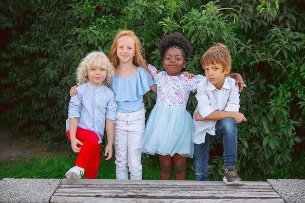 Interraciale groep kinderen, meisjes en jongens die samen spelen in het park in de zomerdag