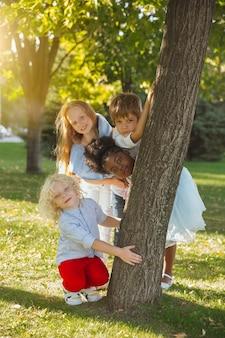 Interraciale groep kinderen, meisjes en jongens die samen spelen in het park