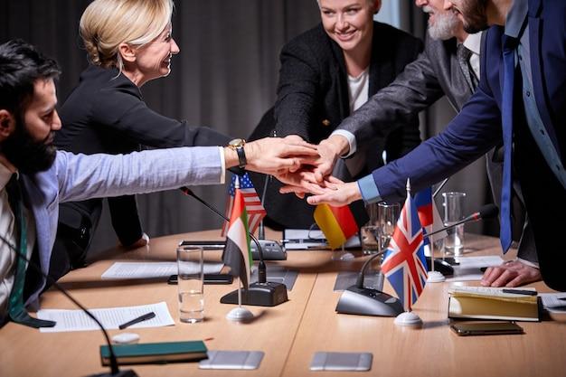 Interraciale groep leidinggevenden hand in hand, succesvol werk, ondertekenen een overeenkomst. in het kantoor