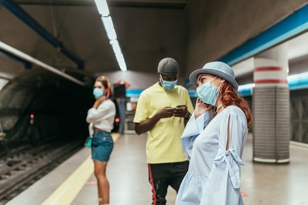 Interraciale groep mensen die met chirurgisch masker op de metro wachten. er is een zwarte man tussen roodharige en donkerbruine vrouwen op het metrostation. de mens gebruikt smartphone.