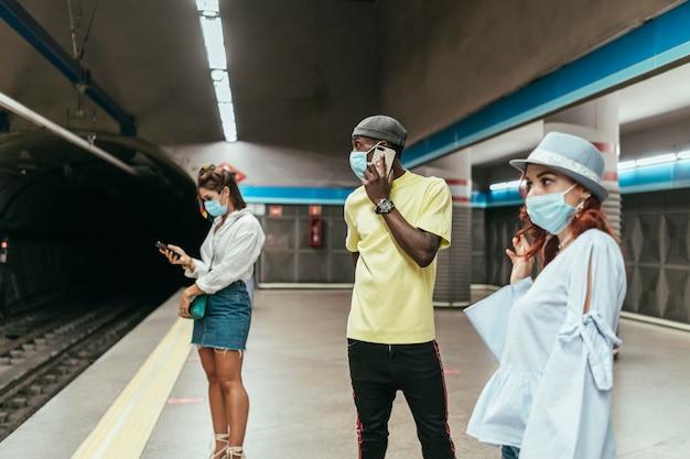 Interraciale groep mensen die met chirurgisch masker op de metro wachten. er is een zwarte man tussen roodharige en donkerbruine vrouwen op het metrostation. de mens spreekt op smartphone.