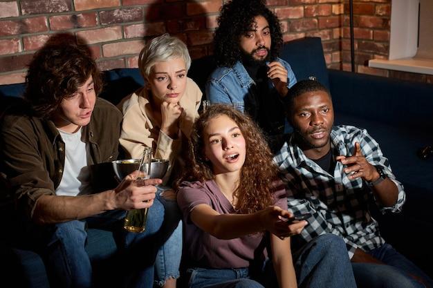 Interraciale groep vrienden bespreken welke film ze moeten kijken, thuis op de bank zitten, de meest interessante film kiezen, ontspannen jongens en dames praten, van zender wisselen op tv