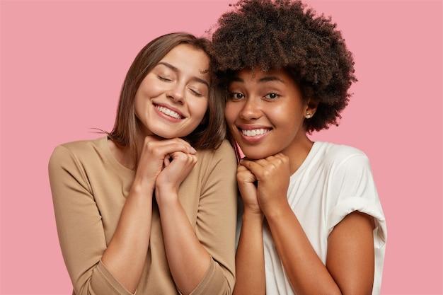 Interraciale jonge vrouwen of zussen voelen hechtheid en steun, hebben goede relaties, glimlachen vreugdevol en houden de handen bij elkaar onder de kin
