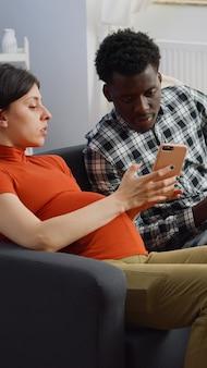 Interraciale ouders zitten in de woonkamer en verwachten een kind