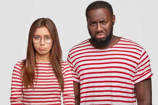 Interraciale relatie concept. ontevreden man met een donkere huid en ontevredenheid van zijn vriendin