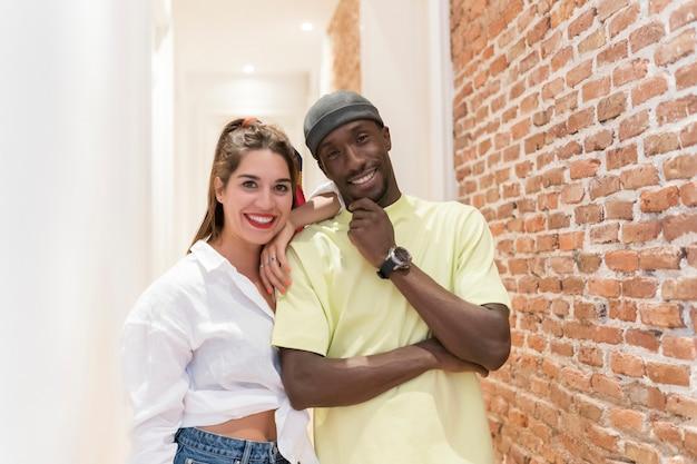 Interraciale vrienden kijken. ze dragen heldere kleren. bakstenen muur en witte gang