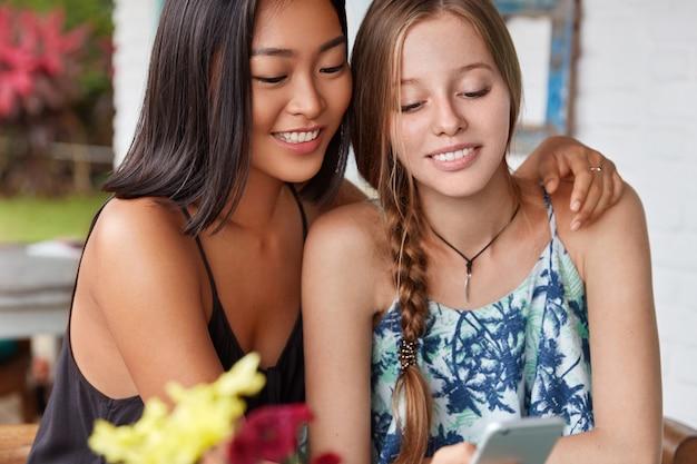 Interraciale vriendinnen besteden vrije tijd samen in gezellig café