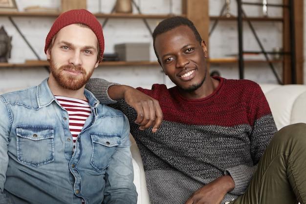 Interraciale vriendschap concept. gelukkig afro-amerikaanse man in casual trui rusten elleboog op de schouder van zijn beste vriend zittend op een witte bank in de coffeeshop, praten en plezier samen
