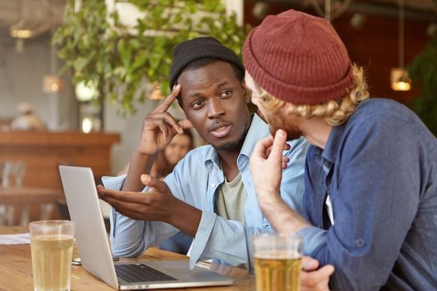 Interraciale vriendschap concept. twee beste vrienden dragen hoeden aan cafétafel zitten en praten, plannen bespreken, nieuws delen, bier drinken en voetbalwedstrijd kijken op generieke latopcomputer