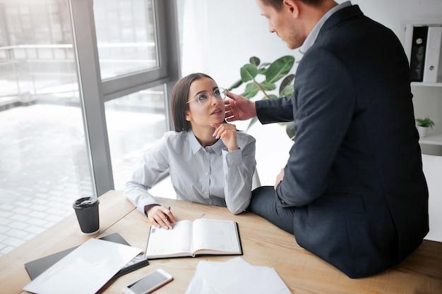 Intieme foto van mooie jonge vrouw zit aan tafel en kijk naar haar baas.