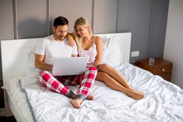 Intieme liefhebbers met behulp van laptop zittend op het bed in de slaapkamer