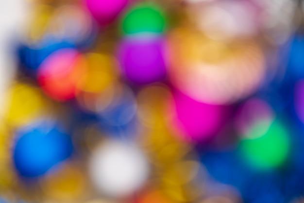 Intreepupil gloeiende kerstballen vakantie decoraties, abstracte wazig bokeh achtergrond effect. onscherpe kleurrijke happy new year lichten viering textuur voor gebruik bij grafisch ontwerp.