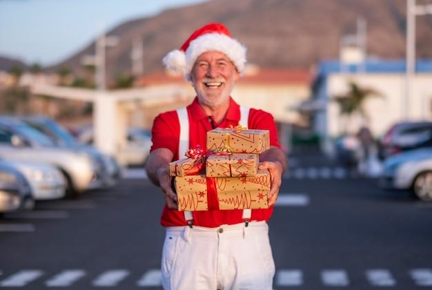 Intreepupil lachende senior man die kerstcadeaus vasthoudt en naar de camera kijkt