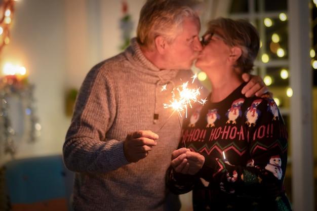 Intreepupil senior paar zoenen vieren kerstevenement met vonken. lichtjes en kerstboom op de achtergrond - actieve gepensioneerde verliefde bejaarden