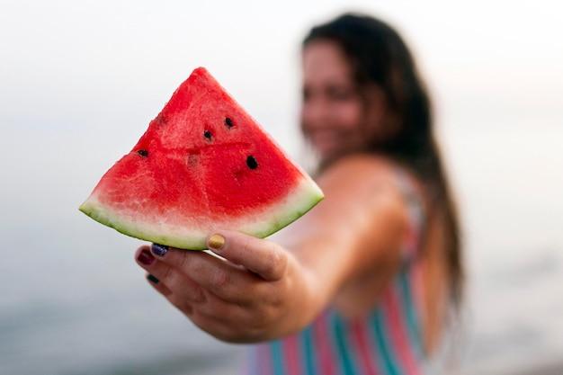 Intreepupil vrouw in het water op het strand met watermeloen