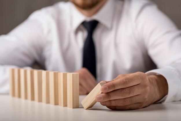 Intreepupil zakenman in pak en stropdas met dominostenen