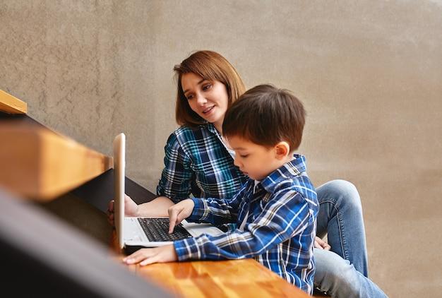 Inventieve moderne moeder met kinderen multitasking in de ochtend. moeder en baby zijn moderne technologieën en gadgets. thuis werken in de omleiding.