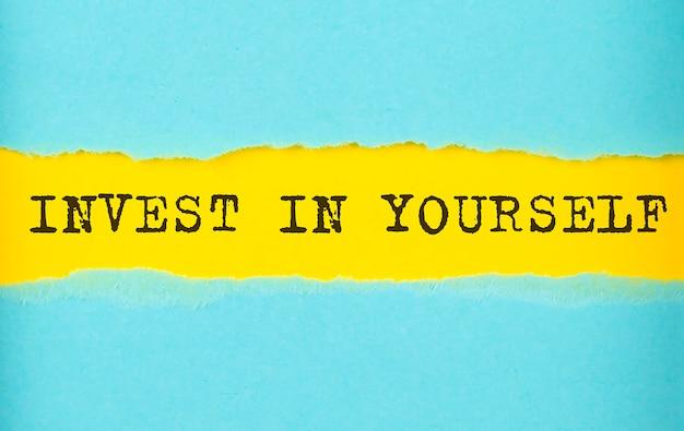 Investeer in jezelf tekst op het gescheurde papier, gele achtergrond